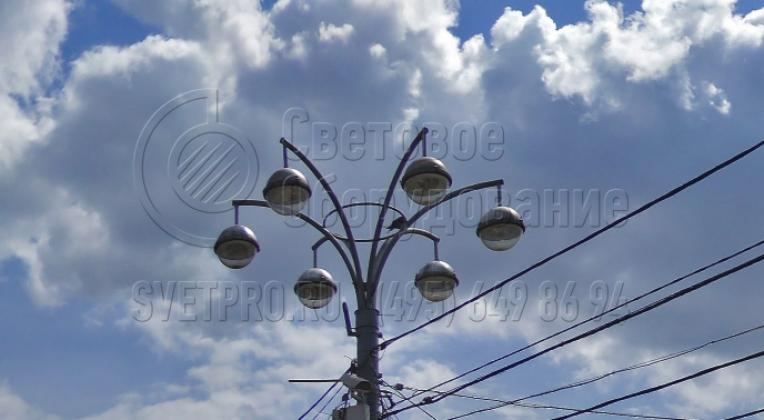 Представленный на изображении кронштейн предназначен для размещения на опорах наружного освещения световых приборов подвесного типа. Они имеют монтажное отверстие в верхней части корпуса. Количество СП на одной осветительной конструкции зависит от числа рожков используемого кронштейна.