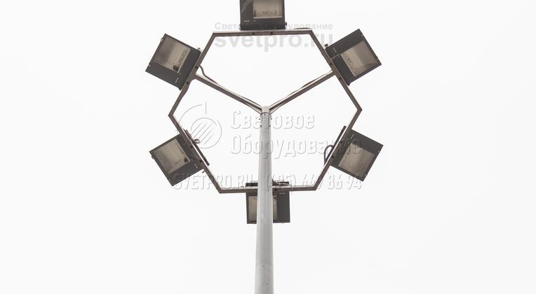 На этом изображении представлен кронштейн с многогранной рамой под прожекторы. Он установлен на опоре конусовидной формы с круглым сечением. Для монтажа использовалась хвостовая часть. Провода проложены по соединяющим горизонтальным элементам, прожекторы закреплены за скобы.