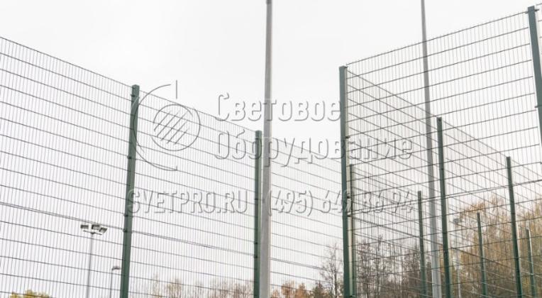 На изображении приведен пример использования Т-образного кронштейна для установки 3 прожекторов, которые освещают футбольное поле. Третий световой прибор закрепляется на дополнительной детали, которая приварена к горизонтальному элементу.