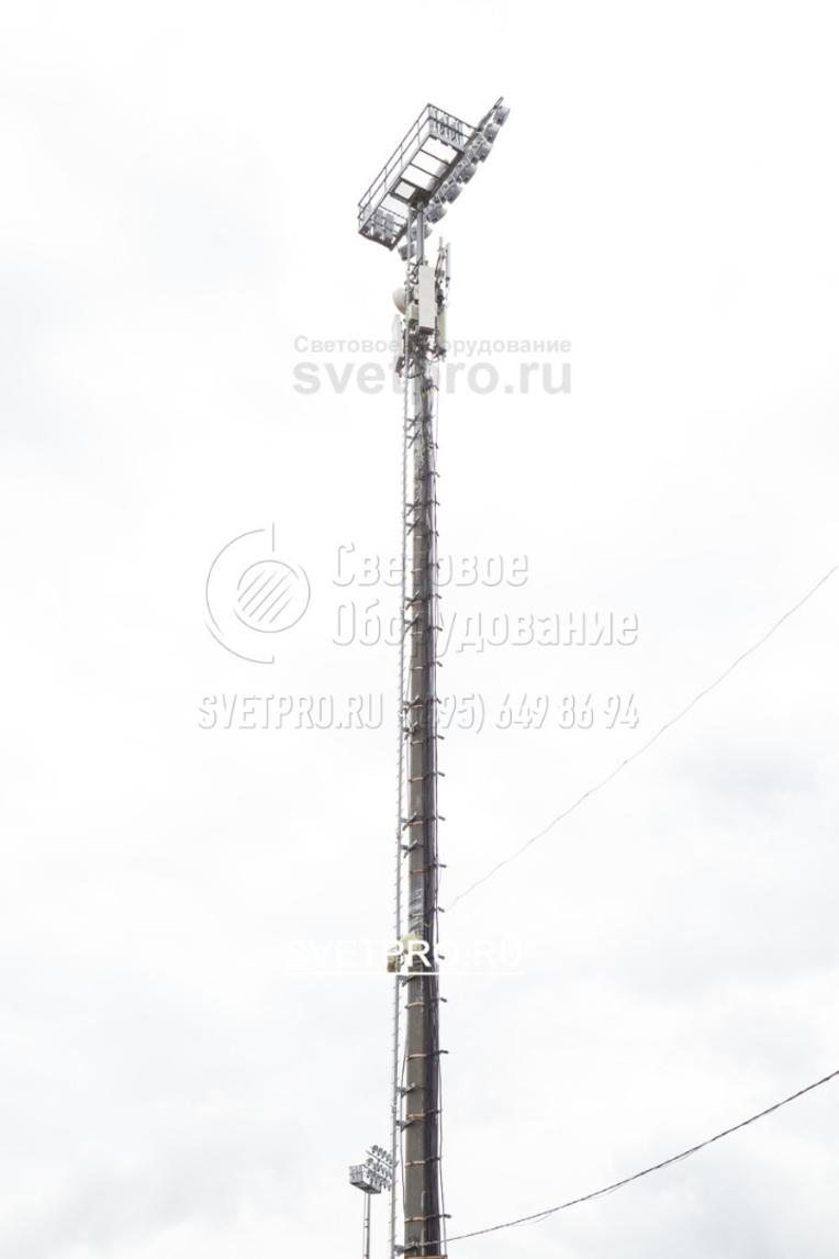 Мачту, которая обычно применяется для освещения площадок, можно использовать для монтажа ретрансляционного оборудования. В примере на изображении под технической площадкой для прожекторов установлены антенны систем сотовой связи. Производитель изготавливает опоры такого типа индивидуально.