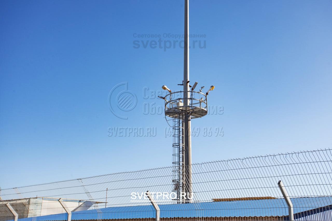 Стационарная рама прочно закреплена на нижнем сегменте мачты, поэтому выдерживает большую нагрузку от установленного оборудования. В примере на фото на ограждении нижней рамы установлены приборы освещения, камеры наблюдения, а также громкоговорители системы оповещения.