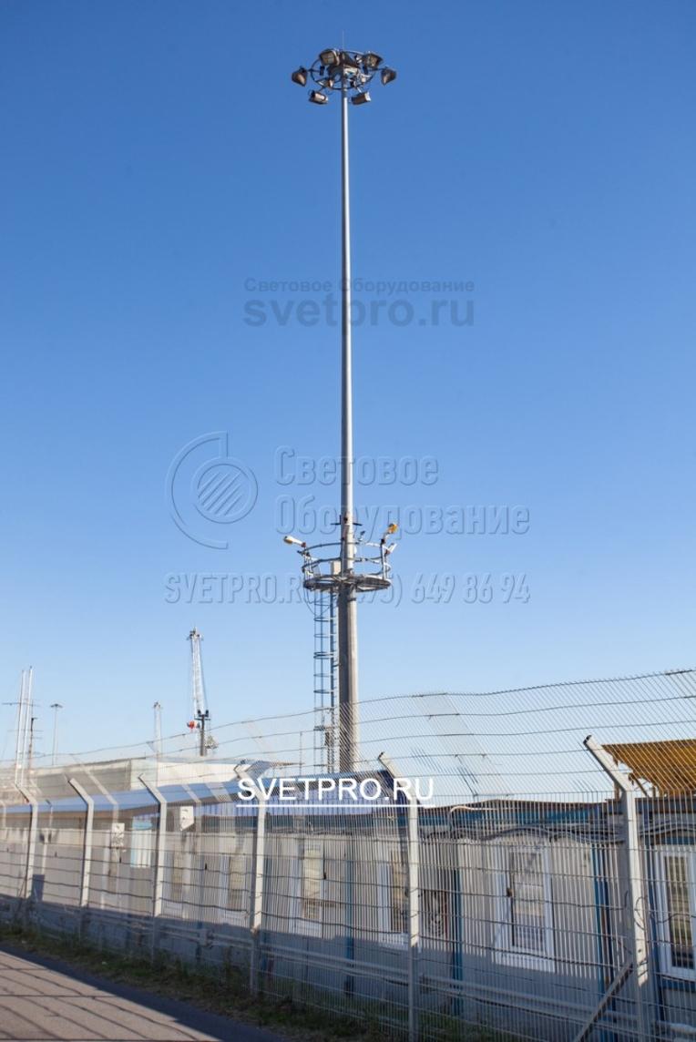 Стационарная площадка на инженерной опоре, представленной на изображении, облегчает обслуживание светильников на спускаемой раме. Спущенная корона не мешает движению транспорта рядом с мачтой. Для доступа на стационарную площадку используется лестница с предохранительной рамой.