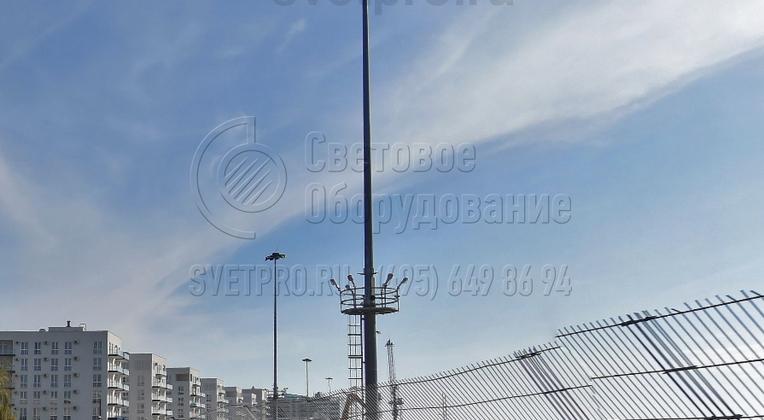 На представленном изображении вы видите мачту, у которой в нижней части имеется неподвижная техническая площадка, а в верхней — спускаемая рама для размещения световых приборов. Такие конструкции устанавливаются на объектах, где предполагается постоянное движение транспорта рядом с мачтой.
