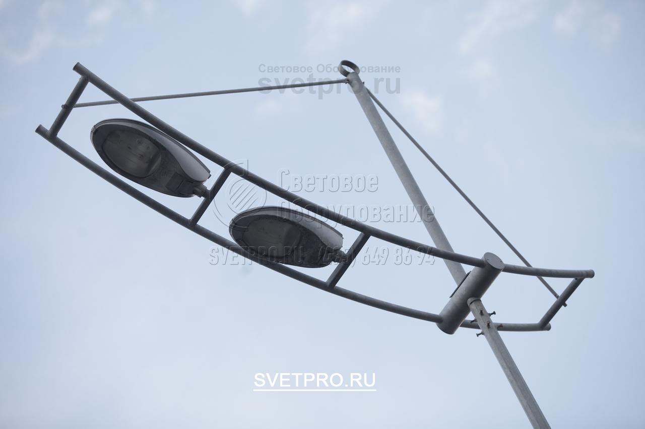 На изображении представлен декоративный кронштейн, установленный на верхушке опоры с граненым корпусом. Этот кронштейн имеет два изогнутых рожка, соединенных друг с другом поперечинами. На них установлены световые приборы с газоразрядными лампами.