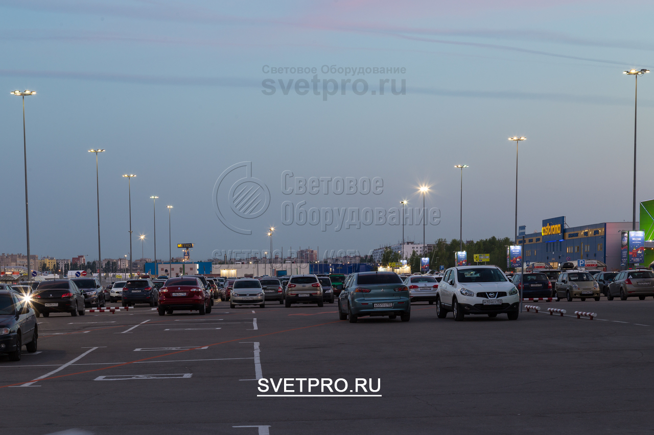 На изображении приведен пример использования опор ОГК с высотой в 16 метров для освещения парковки перед крупным торговым центром. На верхушках установлены многогранные кронштейны для крепления прожекторов с направленным световым лучом.