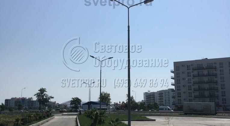 На изображении представлены опоры, которые применяются для освещения парковки и подъездной дороги к ней. На одном стволе установлено два СП  на консолях, которые смотрят в разные стороны. Такой подход дает возможность сократить число конструкций для освещения на территории.