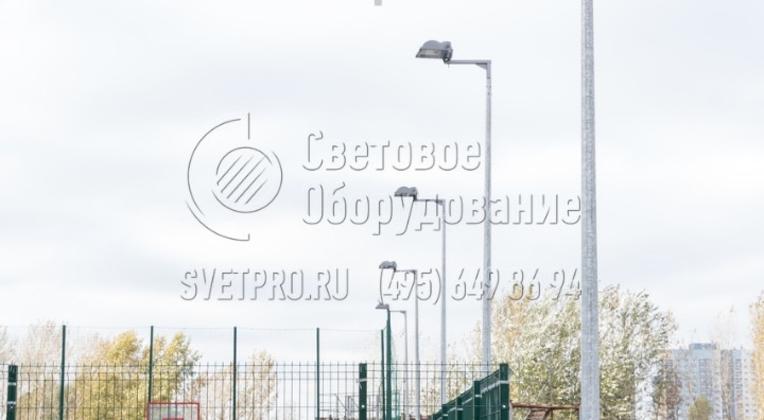 Опора на фото применяется для освещения спортивной площадки в спальном районе города. Так как для защиты от коррозии используется цинковое покрытие, управляющей компании не нужно нести дополнительные затраты на покраску конструкций. Защитный слой сохраняет целостность до 15 лет.