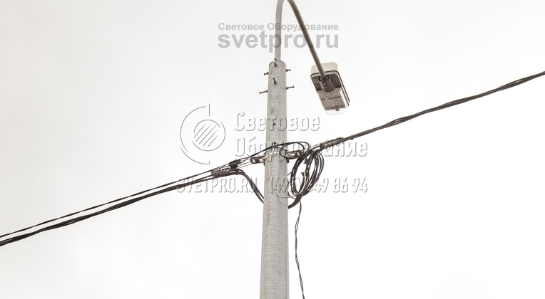 Использование силовых опор позволяет подводить кабели для подачи питания по воздуху и не рыть траншеи. Для крепления используется подвесная арматура, поэтому вносить изменения в конструкцию не нужно. Обратите внимание, что провод к светильнику расположен внутри полого кронштейна.