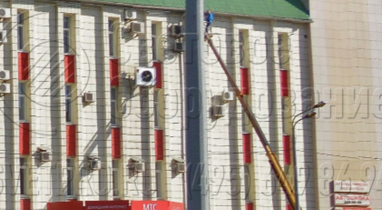 Опора, которая изображена на фото, может выдержать нагрузку до 1300 кг. Поэтому на ее верхушке установлено два световых прибора на кронштейне, а также подвешен силовой кабель и растяжка для крепления рекламных баннеров. Опора надежно закреплена на месте с помощью фланца и ЗДФ.