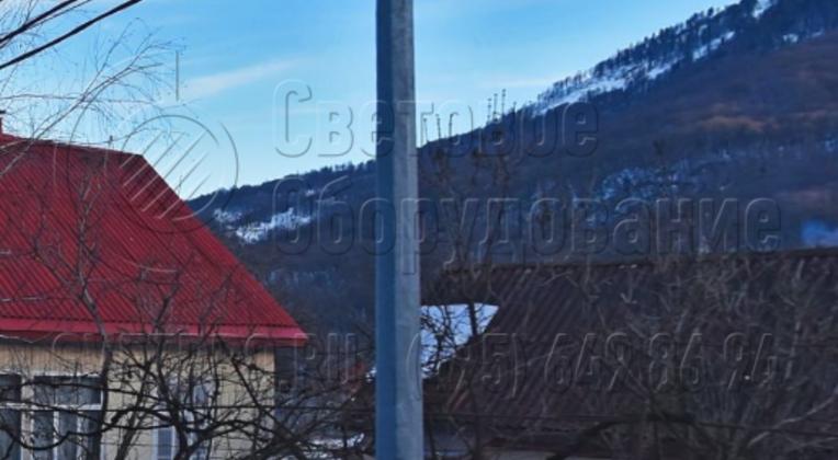 Прямостоечные осветительные опоры часто используются только как конструкции для удержания силовых проводов. В примере на фото на оголовке нет кронштейна со световым прибором. В нижней части отсутствует фланец. Поэтому вплотную к стволу можно ставить забор, высаживать траву на газоне.