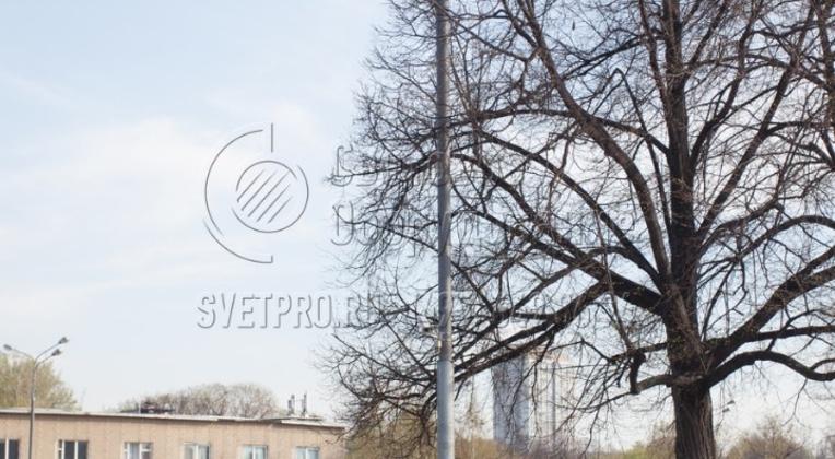 На верхушке опоры типа СФ, изображенной на фото, установлен красивый кронштейн с 4 длинными рожками, расположенными попарно. Это изделие установлено в парке и используется для создания заливающего освещения вокруг. Обратите внимание, что силовые кабели подведены под землей.