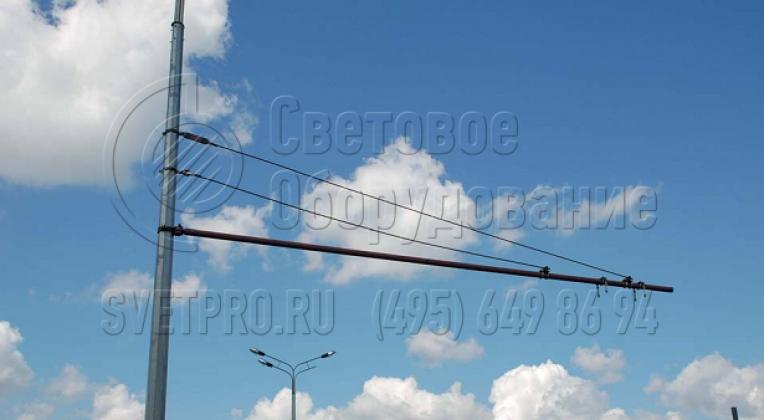 На фото изображена специализированная конструкция с граненым стволом для прокладки контактной сети троллейбусов. В этом варианте используется жесткая консоль, которая удерживается двумя тросовыми растяжками. Так можно закрепить провода к одной опоре, а не двум противоположным.