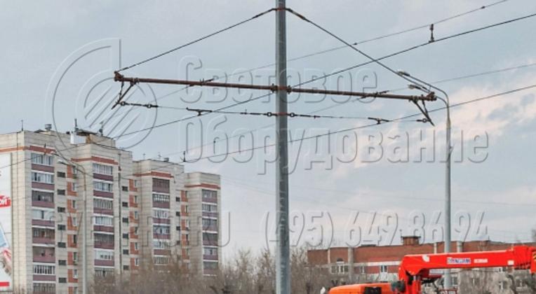 На фото приведен пример использования граненой опоры, к которой подвешивается две линии контактной сети для работы трамвая. Так как корпус имеет большую несущую способность, к нему прикреплены сразу две стальные консоли с растяжками. Это позволяет сэкономить на строительстве.