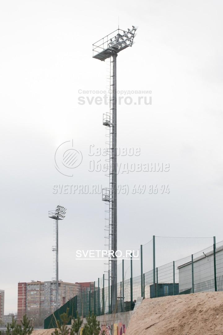 На представленном изображении хорошо видны приспособления, которые обеспечивают безопасность электрика, поднимающегося наверх. Лестница оснащена защитной рамой полукруглой формы. Промежуточные площадки и технологическая платформа имеют защитные ограждения.