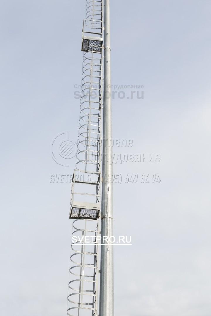 На представленном изображении видна лестница с промежуточными площадками, которая установлена на стволе мачты. Она нужна для того, чтобы выполнять обслуживание светильников без использования автовышек. Площадки позволяют передохнуть при подъеме электрика на большую высоту.