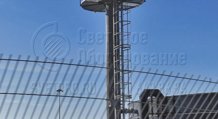 На этом изображении представлен нижний сегмент мачты. Видна стационарная площадка для выполнения ремонтных работ и установки дополнительного оборудования, а также лестница для подъема электриков на нее. Не нужно арендовать автовышки для выполнения ремонтных и регламентных работ.
